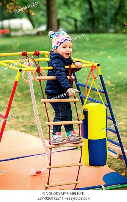The little baby girl playing at outdoor playground against green grass at autumn