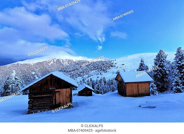 Old snow-covered huts during twilight. Erbe Pass, Funes Valley, South Tyrol, Dolomites, Italy