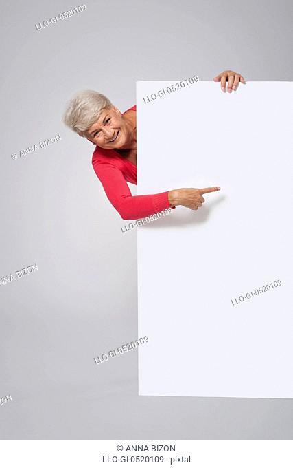 Senior woman showing on empty whiteboard. Debica, Poland&#10