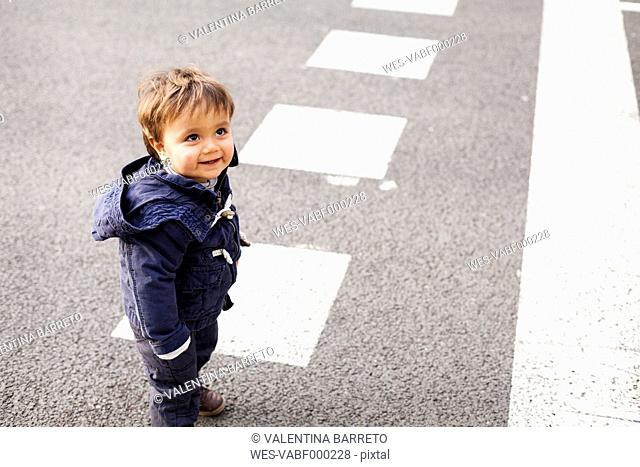 Portrait of smiling little boy standing on a road looking up