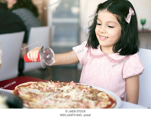 Little girl with oversized pizza in a restaurant