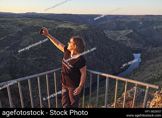A middle-aged woman takes a selfie with her mobile phone in the viewpoint next to the hermitage of Nuestra Señora del Castillo and from which the Duero River...