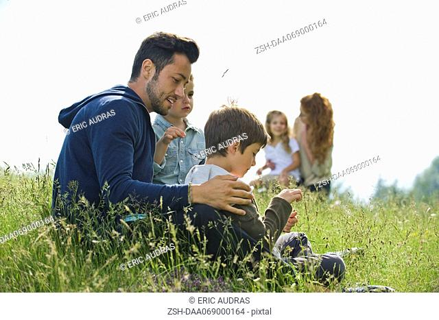 Father talking with young sons outdoors