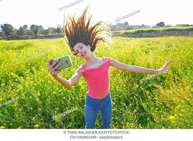 Teen girl selfie video photo in spring meadow moving hair