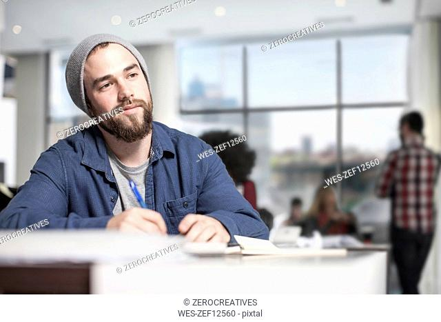 Man with notebook at desk in office thinking