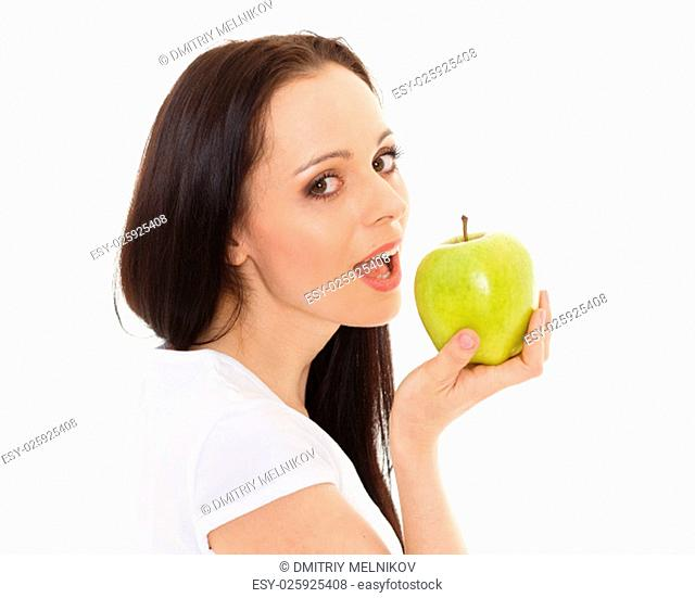 Young beautiful woman with an apple stands on a white background. Concept of healthy food