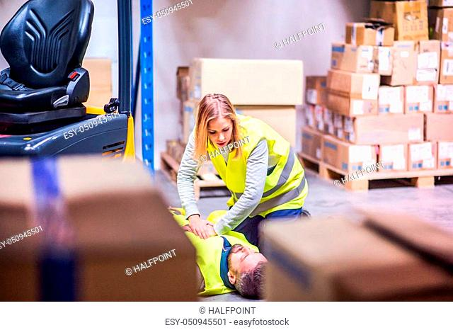 An accident in a warehouse. Woman performing cardiopulmonary resuscitation. Man lying on the floor