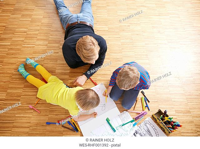 Father lying on floor with children painting