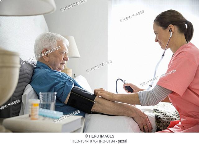 Home care nurse taking senior mans blood pressure