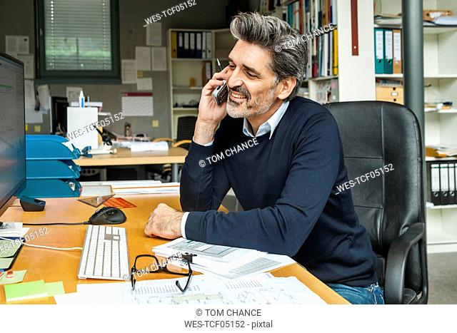 Architect sitting at his desk, talking on the phone