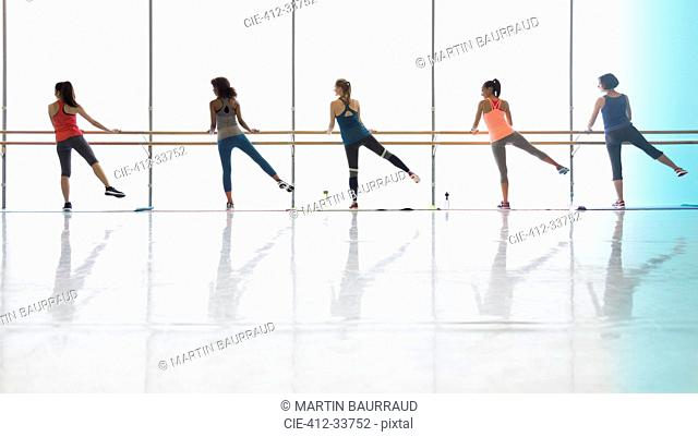 Women exercising at barre in exercise class gym studio