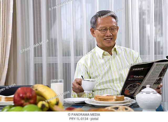 Elderly man reading and drinking