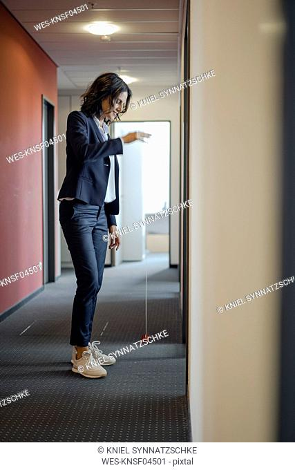 Mature businesswoman standing in office corridor, playing with yoyo
