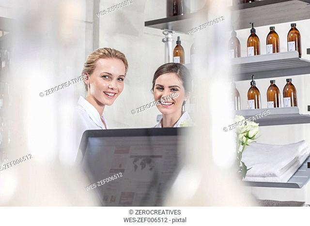 Two smiling shop assistants in wellness shop