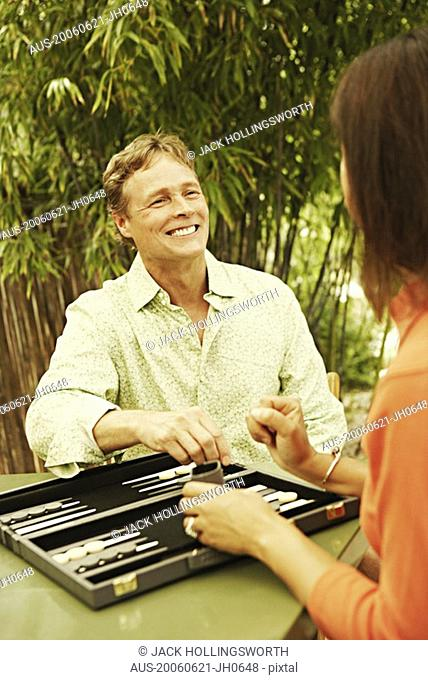 Close-up of a mature man and a mature woman playing backgammon