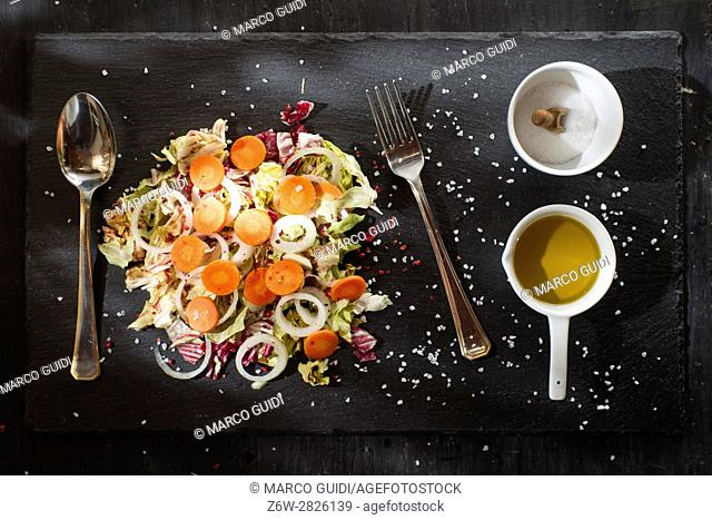 Presentation of a dish of mixed salad on a stone slate
