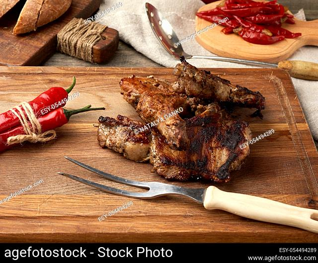 grilled pork steaks on the bone on a kitchen cutting board, baked sliced rye flour bread, top view