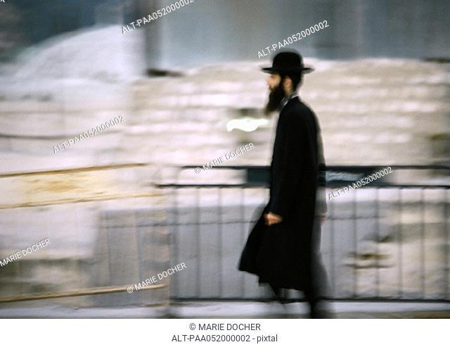 Israel, Jerusalem, Orthodox Jew walking by barrier, side view, blurred