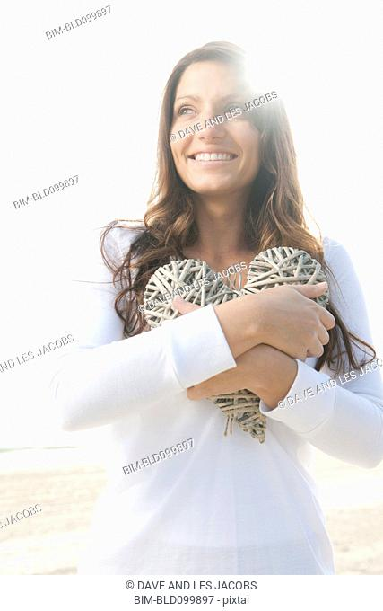 Hispanic woman holding large, woven heart
