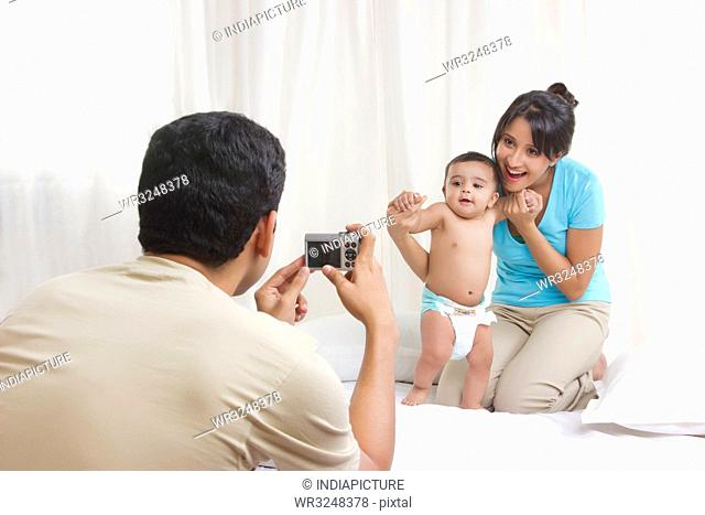 Father taking picture of mother and baby