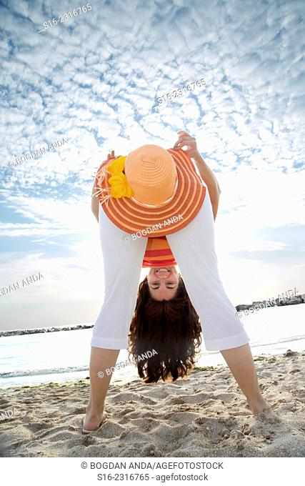 Young woman having fun with a straw hat on the beach