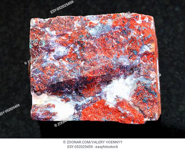 macro shooting of natural mineral rock specimen - rough Jasper stone on dark granite background from South Ural Mountains, Russia