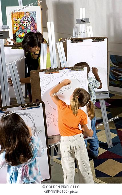 An art teacher with her students drawing on easels in art class