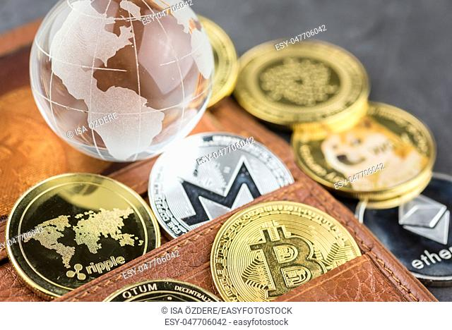 View of different kind of metal bitcoins in brown leather wallet and glass globe . Concept image for cryptocurrency
