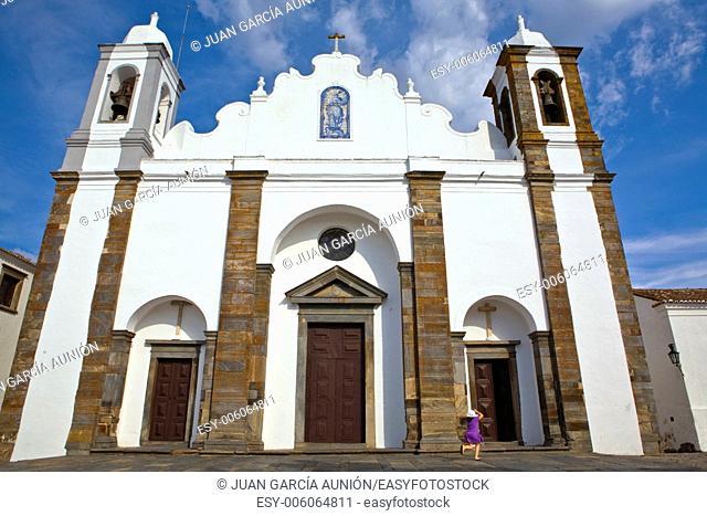 A violet dressed girl rush toward the Church of Nossa Senhora de Lagoa facade, Monsaraz, Portugal