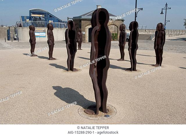 Assembly, by Peter Burke, Woolwich Arsenal, London. Statues standing in a group in an open space. Modern architecture of the Olympic park