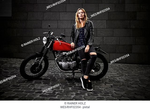 Portrait of confident young woman with motorcycle