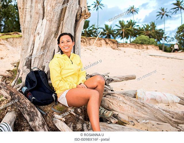 Woman relaxing by old tree trunk, Kailua Beach, Oahu, Hawaii