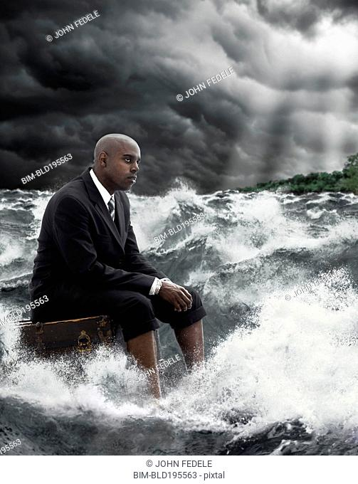 African American businessman sitting on suitcase in stormy sea