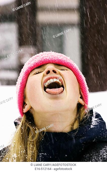 Girl catching snow in mouth