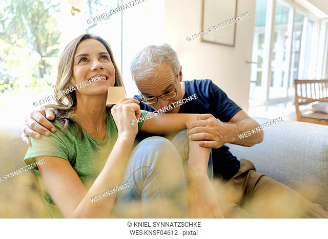 Playful mature man biting in woman's arm holding credit card at home