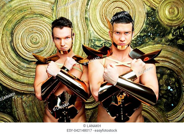 striptease dancers wearing costumes of warriors in the studio isolated against golden studio background