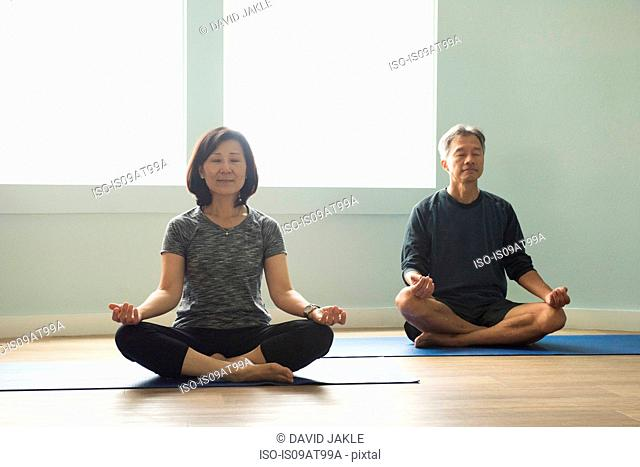 Mature couple sitting cross legged on yoga mat meditating eyes closed