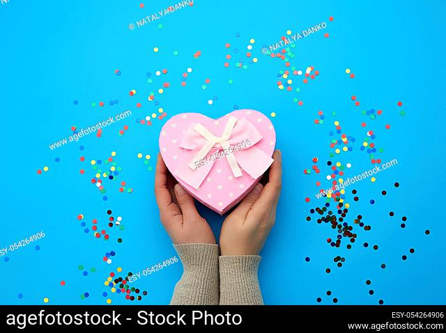 female hand holding a pink cardboard box with a bow on a blue background with multi-colored confetti, concept of giving a gift for a holiday