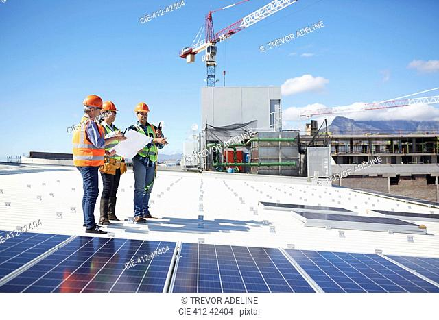 Engineers with blueprint at solar panels at sunny power plant