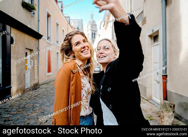 Two female friends taking a selfie in a french touristic town