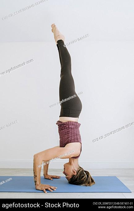Fit muscular athletic woman does headstand while practicing yoga
