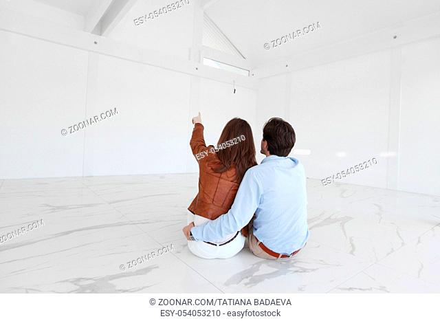Young couple sitting on the floor of new empty house and pointing up into the air