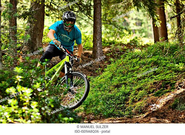 Mountain biker riding off road in forest
