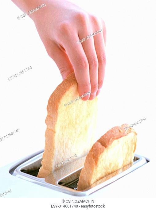hand catches toast bread slices flying out of a toaster
