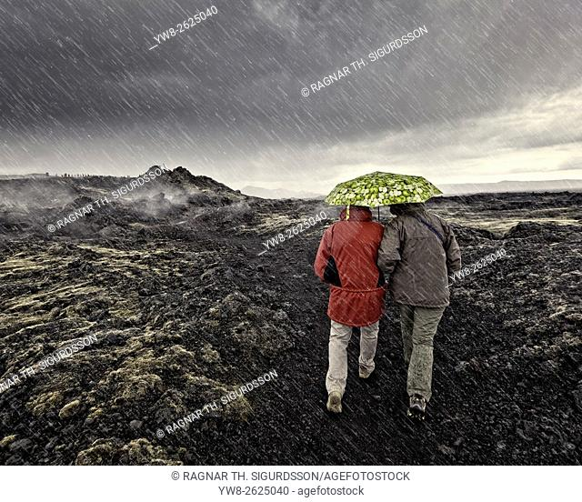 Walking with umbrella, geothermal area by Krafla Geothermal Power plant, Iceland