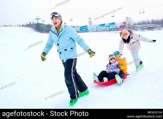 Play snow skateboard happiness of a family of four