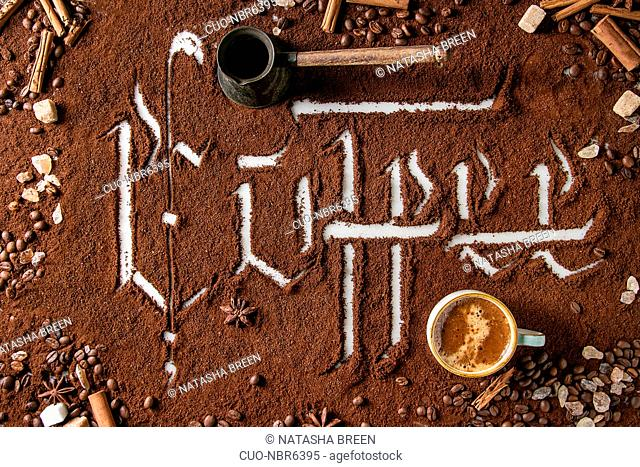 Calligraphic inscription gothic letters coffee over ground black coffee scattered on white marble with roasted beans, pot, cup of espresso