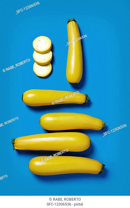 Several yellow zucchinis, whole and sliced