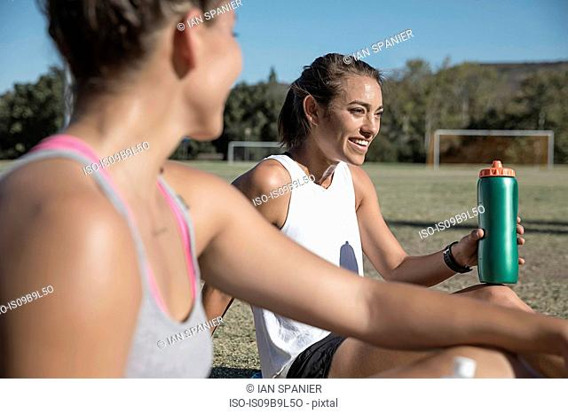 Women sitting on football pitch drinking from water bottle