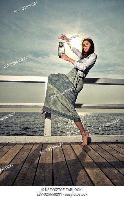 full length young woman on a pier with a kerosene lamp oil. concept carrying light,daylight